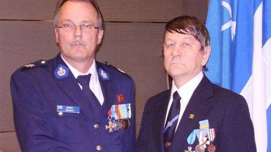 Mikko Kiehelä luovuttaa Nobel-ristin Keijo Kouvoselle.