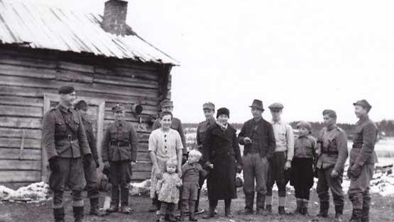 Äiti lapsineen ja muuta Kuoskun kylän väkeä vartijasotilaiden kanssa.