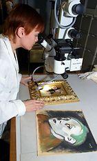 Paperikonservaattori Nora Haikala tutkii mikroskoopilla Schjerfbeckin teoksen aitoutta.