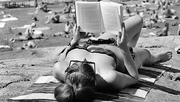 Suomalaisneito ottaa rennosti aurinkoa bikineissä vuonna 1964.