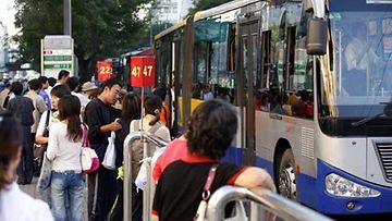Ihmisiä bussipysäkillä Pekingissä.