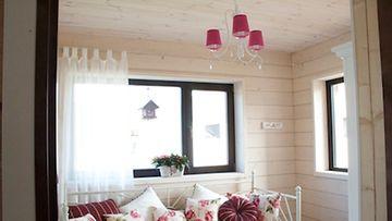 Vierashuone on saanut romanttisen ilmeen kukkakuoseilla ja vaaleilla väreillä. Pinkki kattokruunu istuu siihen saumattomasti.