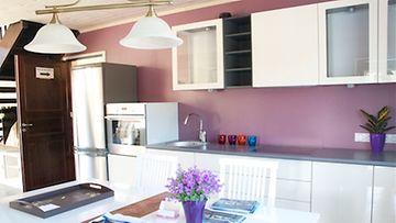 Keittiön takaseinä on trendikkäästi purppura. Linjakkaat tasot tuovat tyyliä kesäkodin keittiöön.