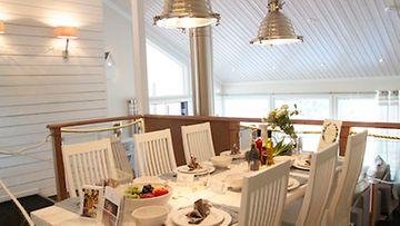 Valkoiseksi maalatut paneelit saavat pienenkin tilan näyttämään väljemmältä. Valkoinen ruokapöytä on katettu kauniin elegantisti.