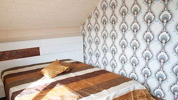 Yksi makuuhuoneen seinistä on tapetoitu nykytrendin mukaisesti kuvioidulla tapetilla. Näyttävä päiväpeitto tuo pieneen huoneeseen särmää. Myös puukuviointi takaseinän paneloinnissa on persoonallinen.