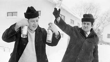 Kaksi suomalaista miestä Keravan Alkon edustalla 26. helmikuuta 1971. Alkon lakko sulki myymälät Helsingissä, mikä aiheutti ryntäyksen Helsingin lähistöllä avoinna oleviin Alkon myymälöihin. Näiden miesten kärsivällinen jonotus palkittiin. Ostoslistalla Dry Vodkaa ja Koskenkorvaa.