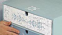 Krakleeraamalla ja oljyväripuikoilla koristeltu lipasto