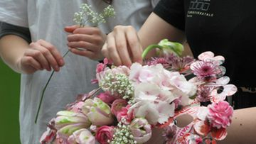 Kukkia asetellaan yksi kerrallaan.