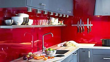 Ikean harmaat keittiönkaapit tasoittavat räiskyvää punaista.