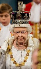 Queen Elizabeth II, wearing the Imperial State Crown, proceeds through the Royal Gallery in the Palace of Westminsterduring the State Opening of Parliament on May 9, 2012 in London, England.