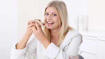 Nainen syömässä aamupalaa.