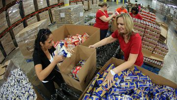 Volunteers fill boxes with nonperishables food items at the Feed the Children distribution center in Oklahoma City, Oklahoma, USA, 22 May 2013. The boxes will be given to various non-profits to help the Moore, Oklahoma tornado victims. The town was hit by a tornado on 20 May killing at least 24 people including seven children in one school.
