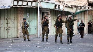 Israeli soldiers take up position during clashes with Palestinian protesters in the West Bank city of Hebron, 27 August 2013. The previous day, three people were killed and six injured after a raid in Qalandiyah, a Palestinian official said.