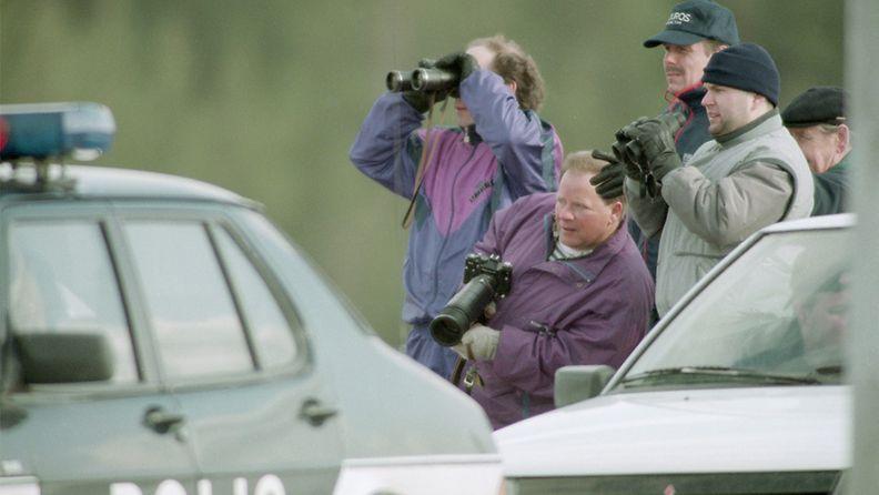 Poliisi piirittää Mika Murasen oletettua piilopaikkaa Karhulassa 19.4.1994. Ihmiset seuraavat tapahtumia. Kymen ilmatorjuntarykmentissä palvellut varusmies Muranen tappoi jalkajousella kolme ihmistä Karhulassa (18. ja 19. huhtikuuta 1994.) ja ammuskeli varuskunnasta varastamallaan rynnäkkökiväärillä ihmisiä kohti