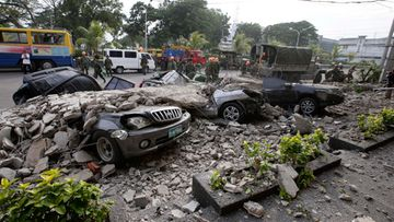 ipino soldiers clear the debris from damaged cars underneath rubble outside a building following a 7.2-magnitude earthquake in Cebu City, central Visayas, Philippines, 15 October 2013.