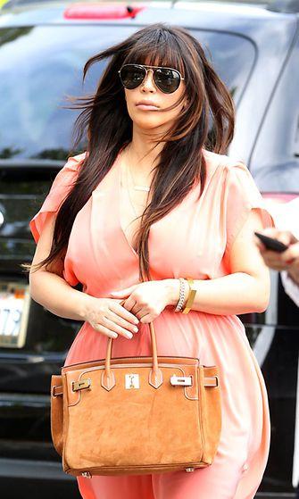 Raskaana oleva tositv-tähti Kim Kardashian persikanvärisessä maksimekossa.