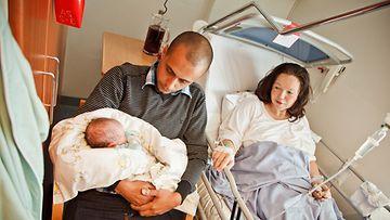Fahmin perhe: isä Mena sylissään pieni Luca-poika, vierellään Sanna-äiti.