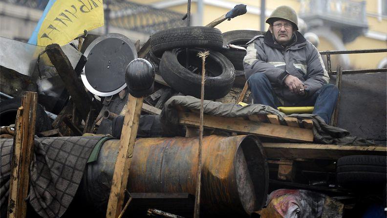 Itsepuolustusjoukkoihin kuuluva mies istui barrikadilla Kiovan keskustassa.