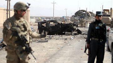 USA:n Nato-joukkoja ja afganistanilaisia poliiseja itsemurhapommin räjähdyspaikalla Kandaharissa eteläisessä Afganistanissa 19. tammikuuta 2012.
