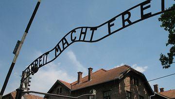 """Auschwitz Birkenau -keskitysleirimuseo Oswiecimissä. Kuvassa sisäänkäynti Auschwitzin keskitysleiriin. Portin yläpuolella on kuuluisa teksti """"Arbeit macht frei""""."""