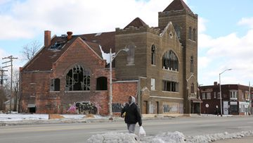 Mies kävelee hylätyn kirkon edustalla Detroitissa maaliskuussa 2013.