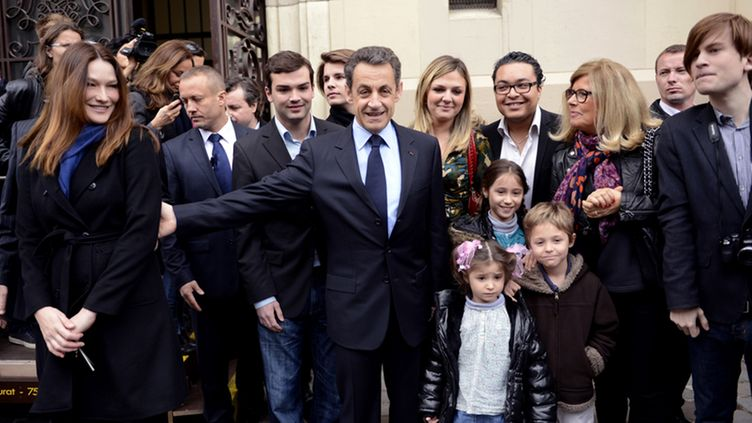 epa03192494 French incumbent President, and 'Union pour un Mouvement Populaire' (UMP) party candidate for the 2012 French Presidential election, Nicolas Sarkozy holds the arm of his wife Carla Bruni-Sarkozy as they leave a polling station in Paris, France, 22 Avril 2012. The second round of France's presidential elections will be held on 06 May 2012.