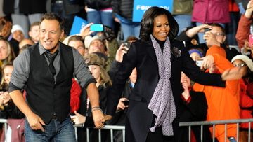 Rock Legend Bruce Springsteen, walks with First Lady Michelle Obama after performing at a huge campaign rally for Democratic candidate for United States President, Barack Obama in Des Moines, Iowa, USA, 05 November 2012. After nearly 18 months of campaigning and after an estimated billion dollars spent, United States President Barack Obama faces Republican candidate for United States President Mitt Romney in the national election on 06 November 2012.