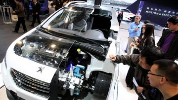 Chinese visitors look at a Peugeot Hybrid Air auto at the 15th Shanghai International Automobile Industry Exhibition at Shanghai New International Expo Center in Shanghai city, China, 20 April 2013. The auto expo will run from 21 to 29 April 2013 in Shanghai, and features some 1,300 autos including 111 cars that will have their premiere at the trade fair.