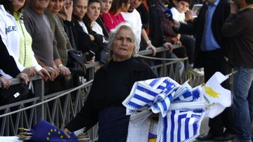 An elderly woman sells flags from Cyprus, Greece and European Union flags during the parade of high school students in front of the Greek Embassy marking the Greek Independence Day in Nicosia, Cyprus, 25 March 2013. Reports state that Cyprus, on 25 March 2013, hammered out a new bailout deal with its international creditors, casting aside a despised bank depositor tax in favour of forced losses on large players in its two biggest lenders.