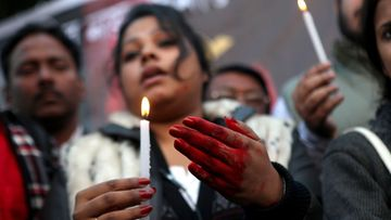An Indian protester, with hands colored in fake blood, holds a candle during a protest campaign by Youth Congress against the gang rape of a student last week, in Calcutta, India, 28 December 2012. The 23-year-old Indian gang rape victim being treated in a Singapore hospital was in extremely critical condition and struggling to survive, doctors said on 28 December. The woman was raped and beaten in a moving bus in New Delhi on 16 December. The attack triggered protests in the Indian capital and other cities.