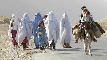 Afgaaninaisia kävelee kadulla burkhat päällä.