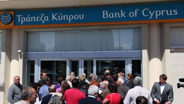 People wait in line in front of a branch of the Bank of Cyprus in Nicosia, Cyprus, 28 March 2013. All of the country's 26 banks were open from 12 pm until 6 pm (1000-1600 GMT) on 28 March with a withdrawal limit set at 300 euros (383 dollars) per person. Cyprus was braced for the reopening of its banks after nearly two weeks, after the government imposed tough capital controls for at least the next seven days. Police were going from bank to bank in central Nicosia to prevent problems, while dozens of people had started to queue in front of the banks' doors.
