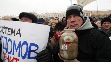 People take part in a rally, with a toy seen inside a glass jar, to protest against the law, passed in late December 2012, that bans US citizens from adopting Russian children at the Marsovo Pole in St. Petersburg, Russia, 13 January 2013. Reports state that thousands of demonstrators gathered for a march in Moscow and St. Petersburg to protest against a ban on US citizens adopting Russian children, saying President Vladimir Putin's government had made orphans pawns in a political dispute. EPA/ANATOLY MALTSEV