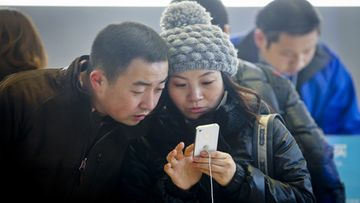 A couple looks at the new iPhone 4s inside an Apple store in Beijing, China, 25 November 2011. China became the world's largest smart phone market by volume according to analysts. China shipped 23.9 million smart phones during the third quarter of 2011, overtaking the U.S. market. EPA/DIEGO AZUBEL