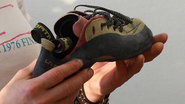 Kiipeilijä Roosa Huhtikorpi esittelee kiipeilykenkää.
