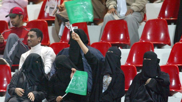 : Saudi Arabia women |wave flags in support of the Saudi soccer team during the match Saudia Arabia vs Oman in Kuwait City at the 16th Gulf Cup soccer tournament Tuesday 06 January 2004. EPA/Raed Qutena