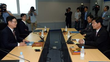 South and North Korean chief delegates shake hands prior to their working-level talks to normalize the crippled cross-border industrial complex in the North Korean border town of Kaesong on 10 July 2013.