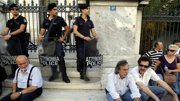 Greek public television and radio ERT employees sit on the steps of the Council of the State building in Athens on 20 June 2013
