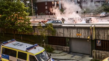 A photo made available on 21 May 2013 shows police officers and firemen beginning repair work to the damage caused by youths rioting in Husby, northern Stockholm, Sweden, 20 May 2013. The youths reportedly set fire to cars and throwing rocks at police, in what is believed to be a protest against the fatal police shooting of a machete-wielding man in the suburb last week.