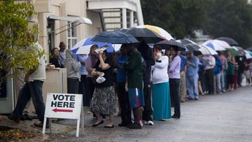 ST. PETERSBURG, FL - NOVEMBER 6: Lines of voters wait in the rain to cast their vote on November 6, 2012 in St. Petersburg, Florida. The swing state of Florida is recognised to be a hotly contested battleground that offers 29 electoral votes, as recent polls predict that the race between U.S. President Barack Obama and Republican presidential candidate Mitt Romney remains tight.