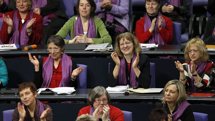 Members of the Left Party faction applaud during a meeting of the German Federal Parliament Bundestag in Berlin, Germany, Thursday, March 8, 2012. The Left Party sent only women wearing a purple scarves to the debate about women's equality in Germany on International Women's Day. (AP Photo/Michael Sohn)  Lehtikuva