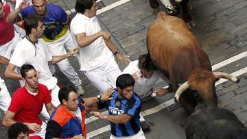 A runner or 'mozo' falls as bulls from Nunez del Cuvillo ranch chase the participants during the last bullrun of the 2011 Sanfermines Fiesta in Pamplona, Spain, 14 July 2011.