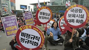 "South Korean female workers shout slogans during a rally to mark International Women's Day in Seoul, South Korea, Thursday, March 8, 2012. The letters read ""Preserve a living wage and hire more temporary employees."" (AP Photo"