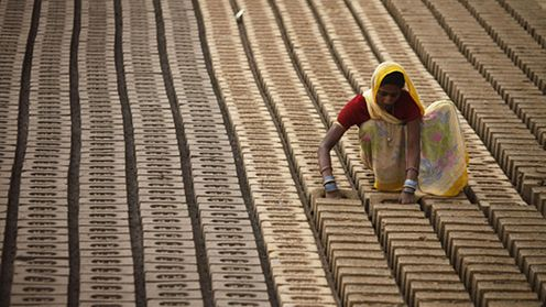 An Indian woman works at a brick factory on the outskirts of Jammu, India,Thursday March 8, 2012. International Women's Day is being marked Thursday. (AP Photo/Channi Anand)