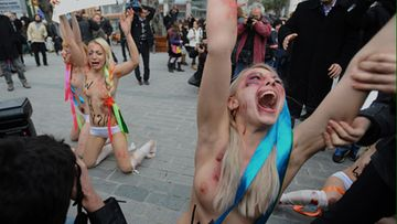 "Police detain one of the Ukrainian women's rights activists as they stage a topless demonstration to protest domestic violence against women in Turkey, in Istanbul, Thursday, March 8, 2012, just hours after a man shot dead a female relative. Four members of the Femen group, wearing makeup to represent injuries, chanted slogans and displayed banners like ""stolen lives"" in the one-minute protest in to mark International Women's Day. (AP Photo)"
