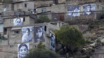 "Pictures of victims of violence are hung on the facades and walls of houses in the neighbourhood of Cerro Gordo in Ecatepec, outside Mexico City March 7, 2012. The Murrieta Foundation opened an exhibition called ""Giving face to the victims in Ecatepec"" with 15 giant photographs placed in different facades and walls of the houses as part a campaign against violence (rape of women, kidnappings, murders and robberies) in Ecatepec. LEHTIKUVA / REUTERS/Henry Romero (MEXICO - Tags: CRIME LAW CIVIL UNREST SOCIETY TPX IMAGES OF THE DAY)"