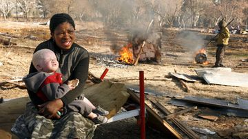 A mother holds her albino daughter to try to keep warm in what remains of her house that was demolished after the squatter community they lived with where evicted from land owned by a mining house, Johannesburg, South Africa, 27 June 2007.