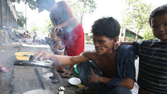 Filippiiniläinen perhe valmistaa riisiä kadulla. (EPA)