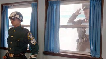 Pohjois- ja Etelä Korean väliin jäävä aselepolinja, Pan Mun Jom, on viimeinen kylmän sodan linnake maailmassa. Kuvassa Etelä -Korean sotilas. Ikkunasta kurkkii uteliaana Pohjois -Korean upseeri. Kuva:Lehtikuva