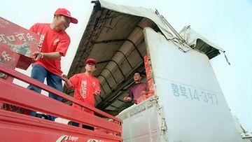 Työntekijät lastaavat Coca-Colaa Pohjois-Koreaan meneviin kuorma-autoihin Kiinan ja Pohjois-Korean rajakaupungissa. Kuva: Lehtikuva